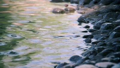 Static close-up peaceful footage of water washing stones
